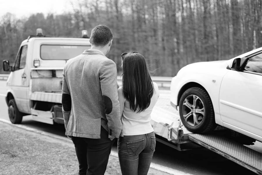 Couple near tow-truck watching vehicle recovery of broken down car